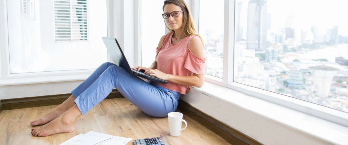 Calm beautiful business lady doing report at home and looking at camera. Confident young financial advisor analyzing papers and sitting on floor. Modern lifestyle concept